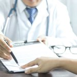 Doctor directing patient to sign a form