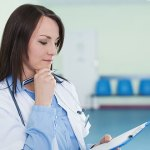 Medical staff member looking at clipboard in waiting room