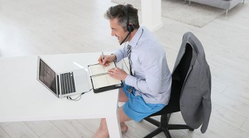 Businessman on video meeting from home in shirt and tie with shorts and flipflops
