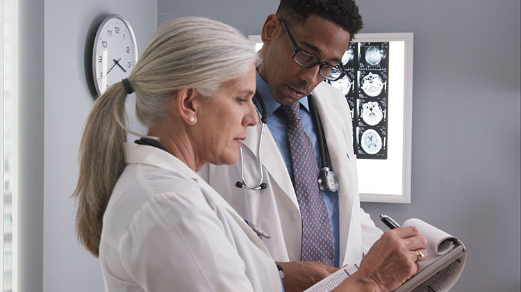 Senior female doctor taking notes of patients ct scan while consulting with young colleague