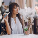 Woman in cafe using e-cigarette