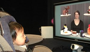 The image shows a baby watching TV.