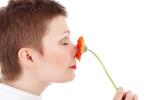 The image shows a woman smelling a flower.