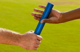 The image shows two hands passing a baton.