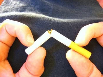 The image shows a person breaking a cigarette.