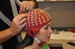 The image shows a study participant being fitted with the EEG cap.