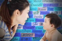 The image shows a woman and a small child in front of a wall covered in words.