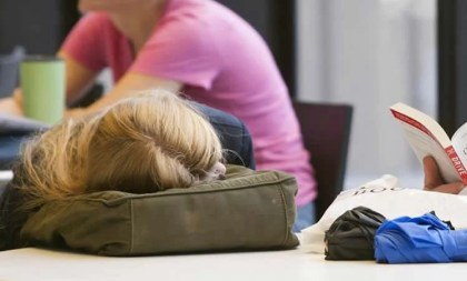 This image shows a teenage girl sleeping on her school bag.