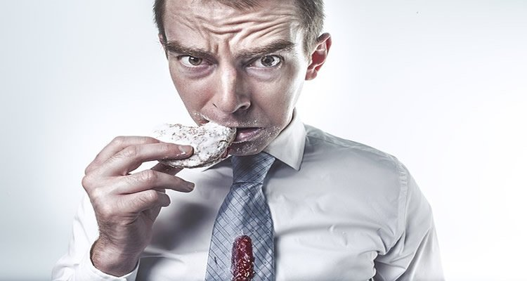 The image shows a stressed looking man eating a sweet donut.