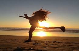 The image shows a girl jumping on a beach.