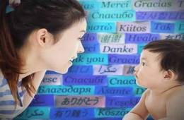This image shows a woman with a baby. Behind them is board full of post-it notes with words in different languages.