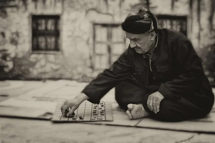 This image shows an old man playing a board game.