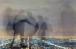 This image shows a cityscape at night with shadow-like human figures over the top.