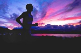 Photo of a man running against a sunset background.