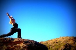 Image of a woman in a yoga pose against a blue sky backdrop.