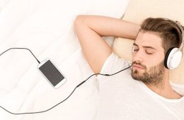 Photo of a man taking a nap while listening to his cell phone via a head set.