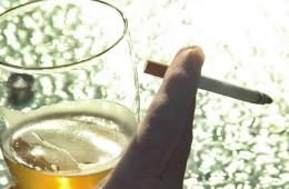 Image of a glass of beer and a cigarette.