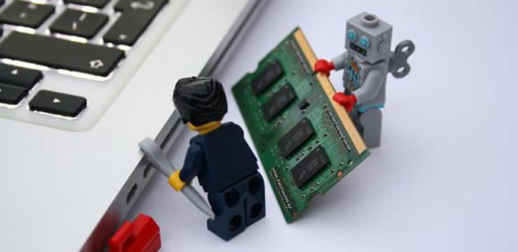 Image shows two Lego figures by a laptop.