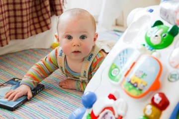 Image shows a baby playing with toys.