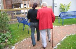 Photo of an old and young person walking.