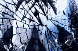 Image shows a man holding his head behind smashed glass.
