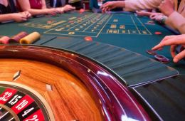 Image shows people gambling around a roulette table.