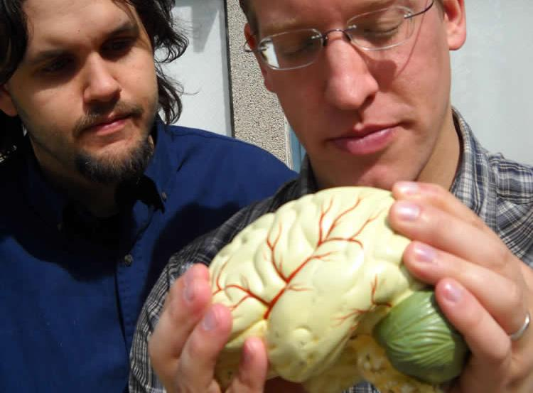 Image shows the researchers holding a brain.