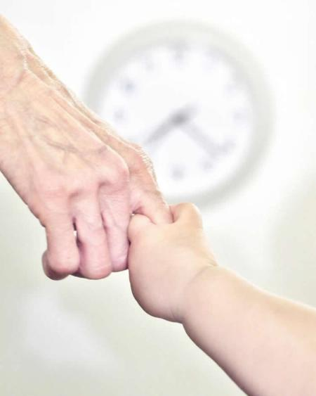 Image shows a young person holding an old person's hand.