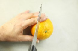 Image shows someone about to cut their finger with a knife while slicing an orange.