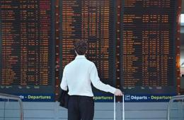 Image shows a man looking at a train departure board.
