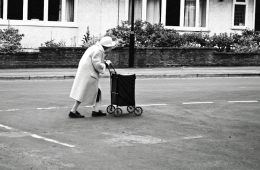 Photo of an old lady crossing a road.