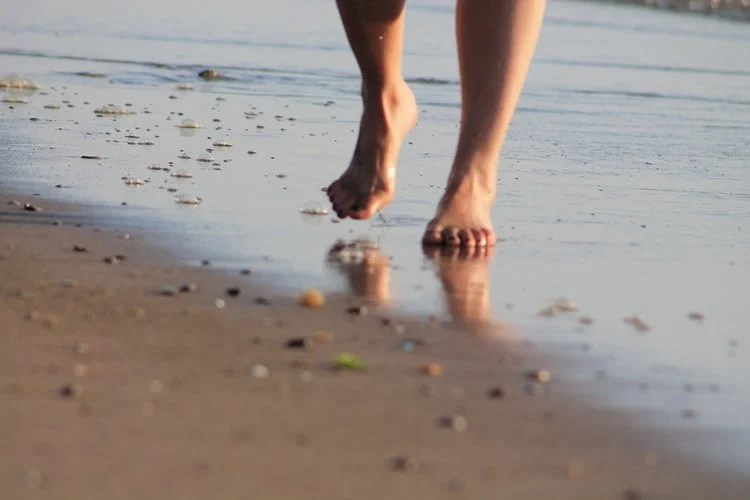 Image shows a person running barefoot on a beach.