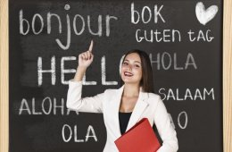 Image shows a woman standing infront of a blackboard with words for Hello written in different languages on it.
