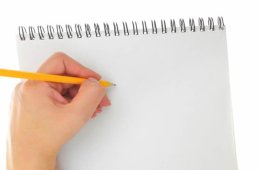 Photo of a person writing left handed.