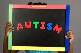 Image shows a person holding up a sign with Autism written on it.