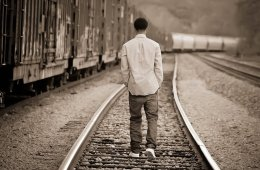 Image shows a teenaged boy walking along a railway track.