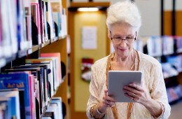 Image shows an older lady reading from a tablet.