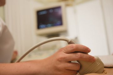 Image shows a woman undergoing an ultrasound.