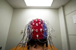 Image shows a person in an EEG cap.