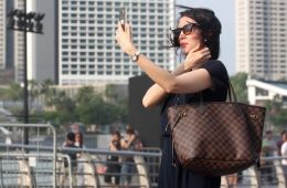 Image shows a woman taking a selfie.