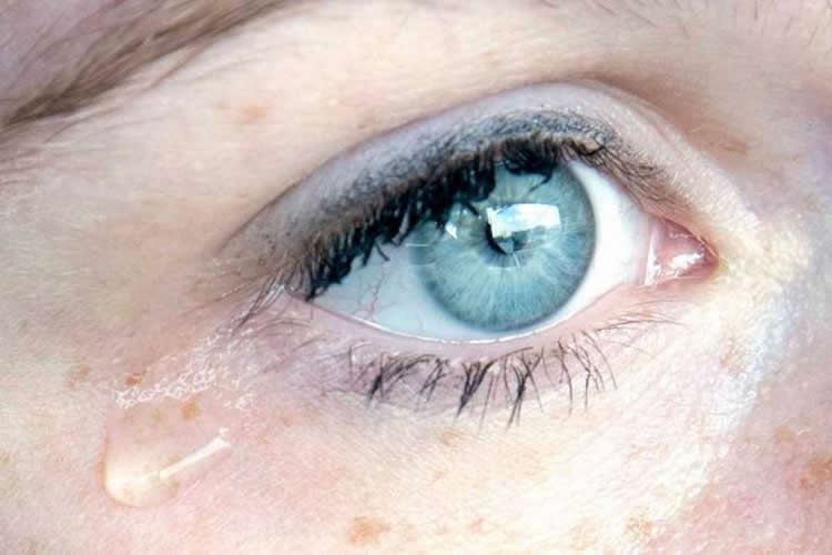 Image shows a woman shedding a tear.