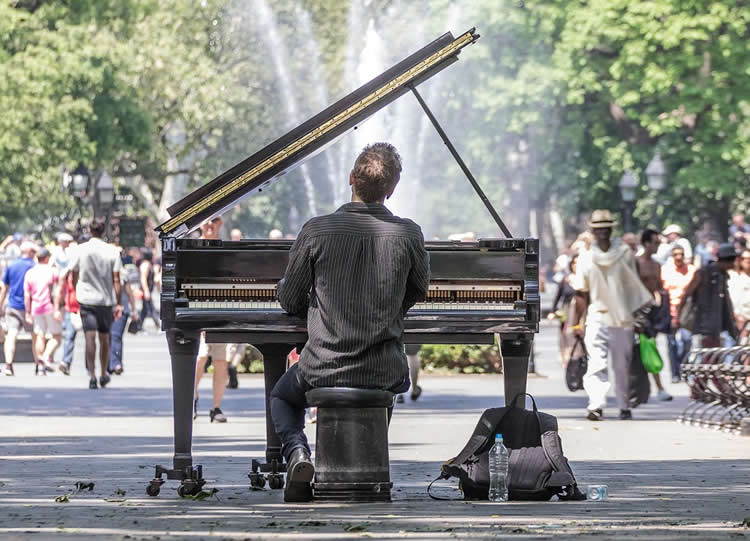 Image shows a man playing piano in a park.