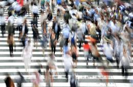 Image shows blurry people crossing a busy street.