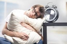 Image shows a man sitting awake with an alarm clock.