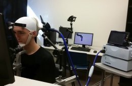 Image shows a person playing the computer game with the brain stimulation device on.