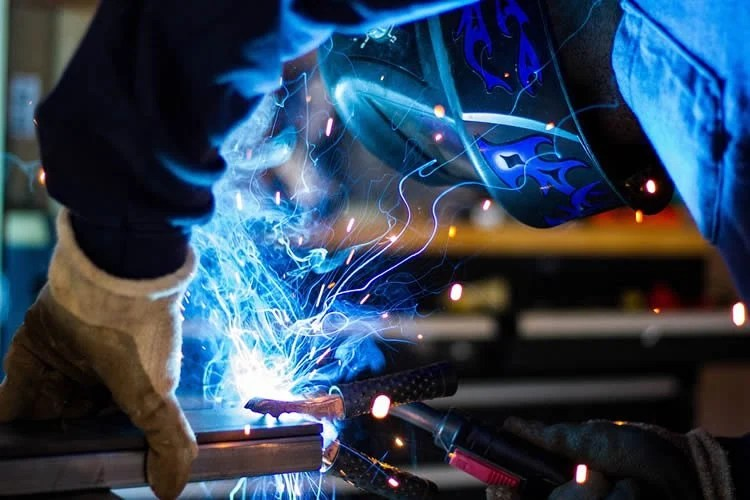 Image shows a person welding.