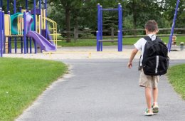 Image shows a little boy walking in a park.