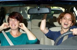 Image shows a woman singing and another woman with her fingers in her ears.