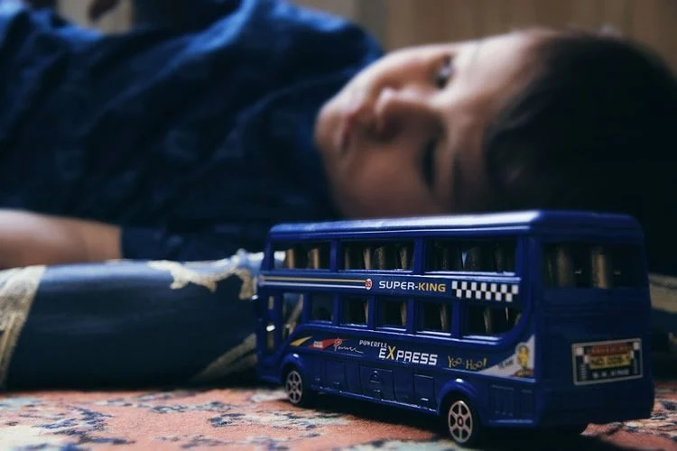 Image shows a child playing alone with a bus.
