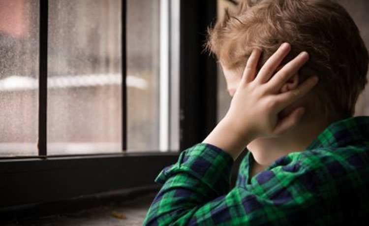 Image shows a boy with his hands over his ears.
